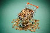Shopping trolley with coins — Stock Photo