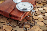 Wallet and pocket watch on coins — Stock Photo
