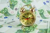 Alarm clock on Euro banknotes — Stock Photo