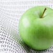Green apple on a binary code — Stock Photo #64320489