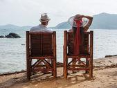 Homem e uma menina sentada na praia — Fotografia Stock