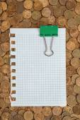 Notepad and binder clip on coins — Stock Photo
