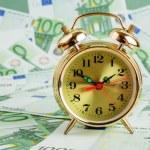 Alarm clock on banknotes — Stock Photo #67582873