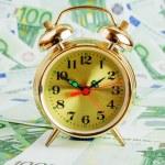 Alarm clock on a Euro banknotes — Stock Photo #73567075