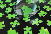 Green puzzles and magnifying glass — Stock Photo