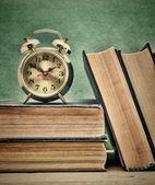 Eski kitaplar ve çalar saat — Stok fotoğraf