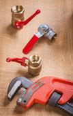 Monkey wrench and plumbing fixtures — Stock Photo