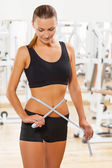 Beautiful female wearing sports clothes measuring waist — Stock Photo