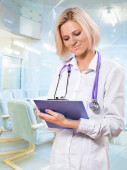 Female doctor clipboard and writing in it — Stock Photo