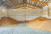 Harvested corns of wheat in old storage house — Stock Photo