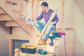 A young construction contractor sitting on steps of wooden ladde — Stock Photo