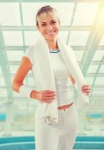 Beautiful sportswoman wearing sports clothes standing and holdin — Stock Photo