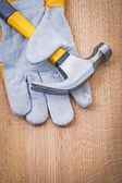 Claw hammer and protective glove on wooden board — Stock Photo