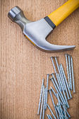 Claw hammer and nails on wooden boards — Stock Photo