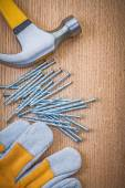 Composition of claw hammer nails and protective glove on wooden — Stock Photo