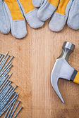 Copyspace image claw hammer nails protective gloves on wooden bo — Stock Photo