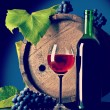 Bottle of wine and wineglass with grape near wooden vintage keg — Photo #57654283