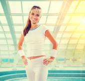 Beautiful smiling young sportswoman wearing sports clothes looki — Stock Photo