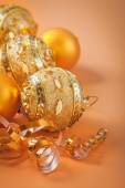 Christmas balls and ribbon on light brown background — Stock Photo