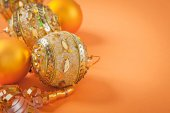 Christmas baubles and ribbon on orange colored background — Stock Photo