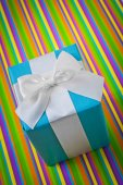 Gift box on striped colored background — Foto de Stock