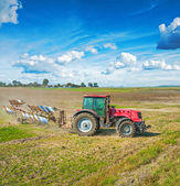 Agriculture processing tractor with plow — Stock Photo