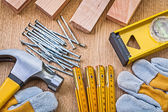 Gloves, hammer, level, nails and planks — Stock Photo