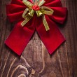 Beautiful red christmas bow with gold ribbon — Stock Photo #61464949