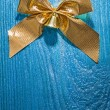 Golden bow on wooden board — Stock Photo #61465079
