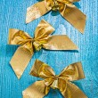 Three golden bows with little bells — Stock Photo #61465101