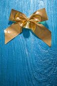 Golden bow on wooden board — Stock Photo