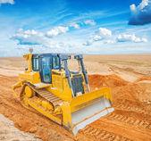 Bulldozer on sand in field — Stock Photo