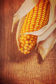 Ear of corn on wooden board — Stock Photo