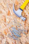 Claw hammer with nails on plywood — Stock Photo