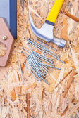 Claw hammer handsaw and nails on plywood — Stock Photo