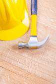 Yellow hardhat and claw hammer — Stock Photo