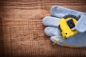 Yellow tapeline in protective glove — Stock Photo