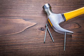 Claw hammer with yellow handle and nails — Stock Photo