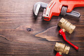 Plumbers tools on vintage wooden board — Stock Photo
