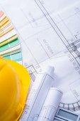 Yellow helmet rolled blueprints — Stock Photo