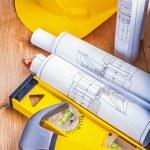 Yellow helmet rolled blueprints — Stock Photo #69018285