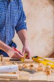 Carpenter drawing on wooden plank — Stock Photo