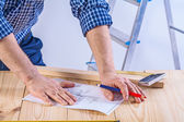 Hands of worker on table — Stock Photo