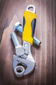 Nut in wrench and bolts on wooden board — Stock Photo
