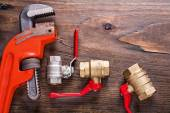 Plumbers fixtures with red handles and monkey wrench on vintage  — Stock Photo