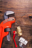 Plumbers fixtures and monkey wrench on vintage wooden board — Stock Photo