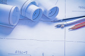 Rolled up blueprints and pencil with compass — Stock Photo