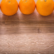 Five oranges on wooden board — Stock Photo #69625825