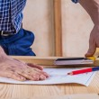 Hands of carpenter on table with blueprint — Stock Photo #69626133