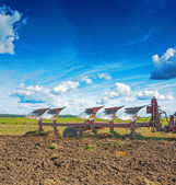 Big plough in work on field — Stock Photo